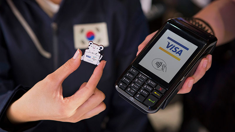 An olympic participant holding a mascot pin and checking out at a store promoting for Visa wearables pin.
